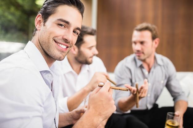 Gruppo di uomini che fumano e bevono mentre discutono
