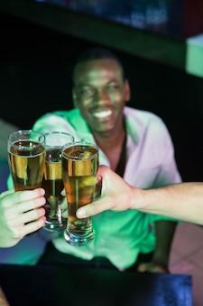 Gruppo di uomini che tostano con un bicchiere di birra nel bar