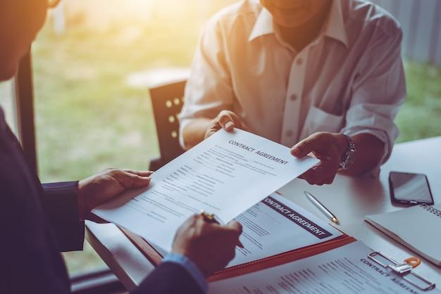 Gruppo di uomini d'affari asiatici di mezza età e avvocati che discutono e firmano un contratto.