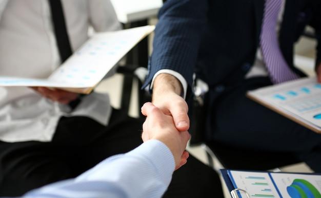 Gruppo di uomini d'affari che agitano le mani dopo una riunione produttiva
