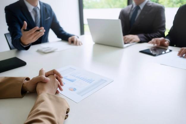 Gruppo di uomini d'affari che discutono di valutazione del bene immobile con il dirigente esecutivo in un ufficio moderno