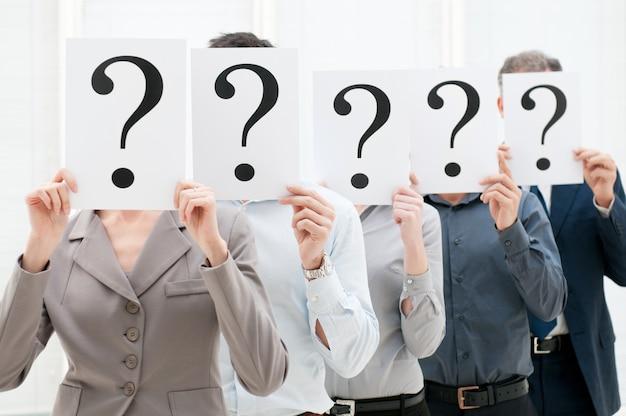 Gruppo di uomini d'affari che nascondono i loro volti dietro un punto interrogativo in ufficio