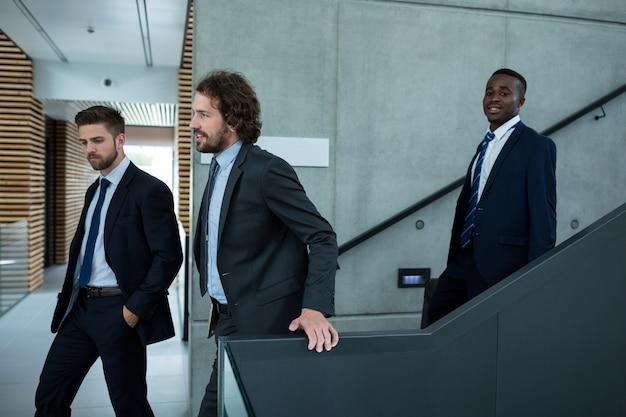 Gruppo di uomini d'affari che scendono le scale