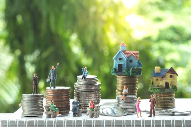 Gruppo di uomini d'affari con file di monete pila e case.