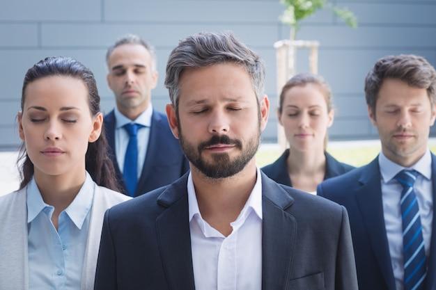 Gruppo di uomini d'affari con gli occhi chiusi