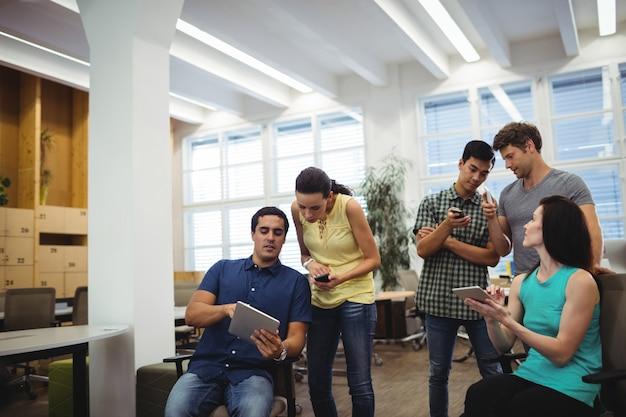 Gruppo di uomini d'affari con tavoletta digitale e telefonini