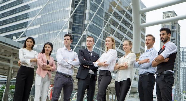 Gruppo di uomini d'affari in piedi all'aperto con braccio incrociato e in attesa di target