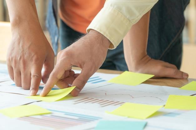Gruppo di uomini d'affari in piedi incontro con i colleghi nella sala riunioni e visualizzare il grafico delle prestazioni annuali