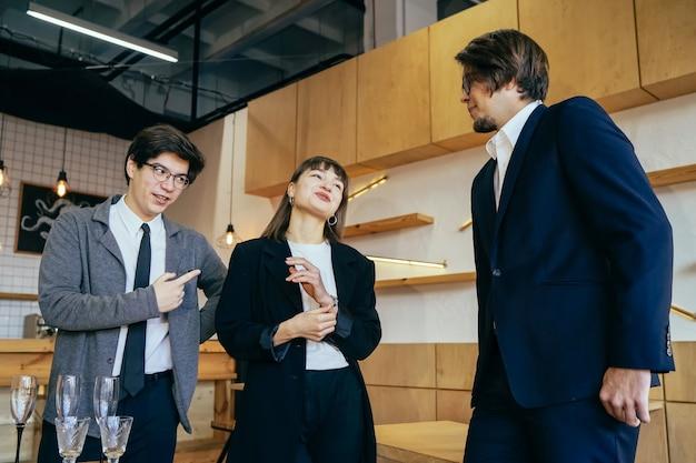 Gruppo di uomini d'affari in una riunione in piedi raggruppati in un ufficio