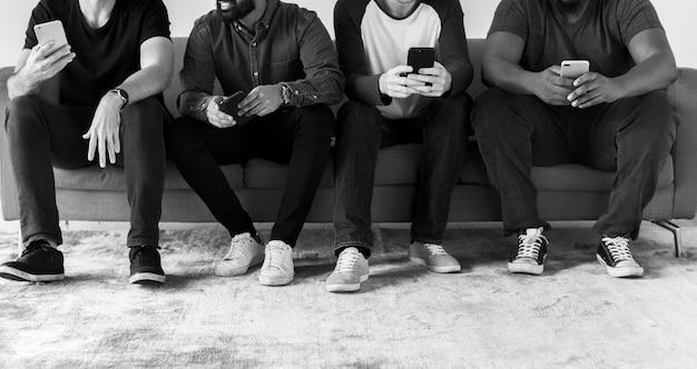 Gruppo di uomini diversi che utilizzano il social media di telefonia mobile e il concetto di internet