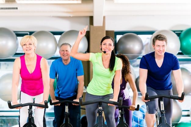 Gruppo di uomini e donne che filano sulle bici di forma fisica in palestra