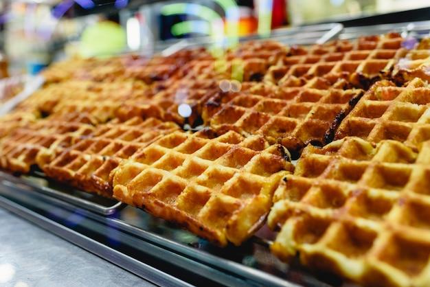 Gruppo di waffle appena sfornati pronti per essere gustati in vendita in una fiera.