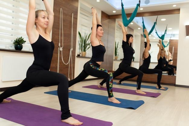 Gruppo di womans facendo esercizi di yoga in palestra. stile di vita in forma e benessere