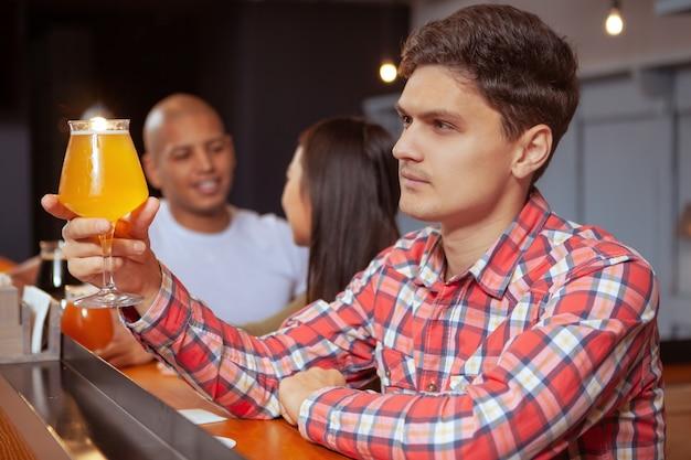 Gruppo eterogeneo di amici che bevono birra al pub insieme