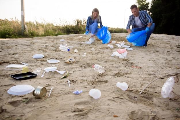 Gruppo eterogeneo di persone che raccolgono i rifiuti nel servizio volontario della comunità del parco.