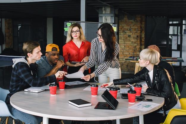 Gruppo eterogeneo multietnico di team creativi, uomini d'affari casuali o studenti universitari in riunioni strategiche o discussioni di brainstorming di progetto in ufficio, utilizzando tablet. concetto di avvio o lavoro di squadra.