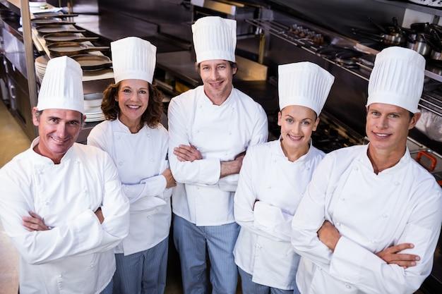 Gruppo felice dei cuochi unici che sta insieme nella cucina commerciale