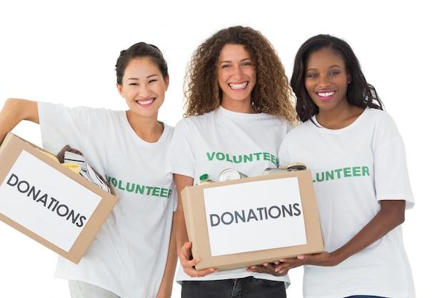 Gruppo felice di volontari che sorridono alle scatole di donazioni della tenuta della macchina fotografica