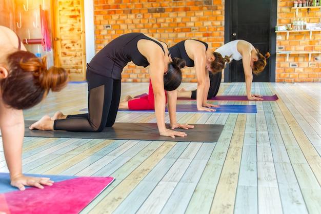 Gruppo femminile asiatico di forma fisica che fa posa di yoga di riscaldamento