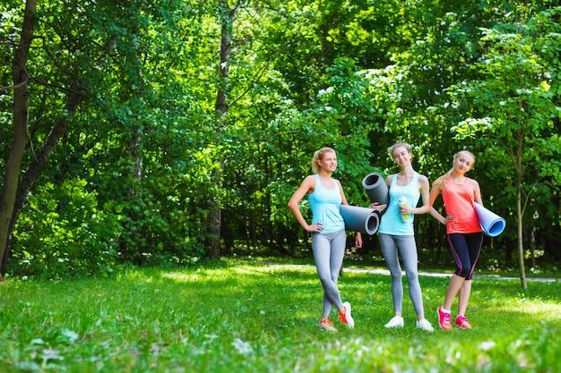 Gruppo femminile di forma fisica in parco un giorno soleggiato. allenamento all'aperto.