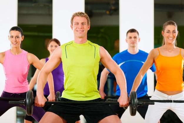 Gruppo fitness con bilanciere in palestra