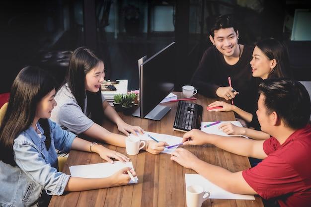 Gruppo indipendente asiatico che spiana per il lavoro di squadra nella sala riunioni dell'ufficio