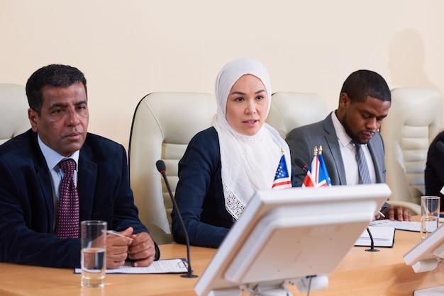 Gruppo interculturale di giovani delegati o uomini d'affari che fanno relazioni alla conferenza e discutono i loro punti