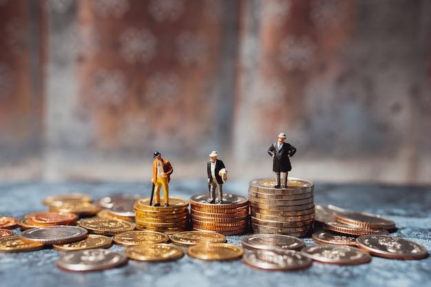 Gruppo miniatura di uomini d'affari che stanno sul mucchio delle monete facendo uso di come finanziario