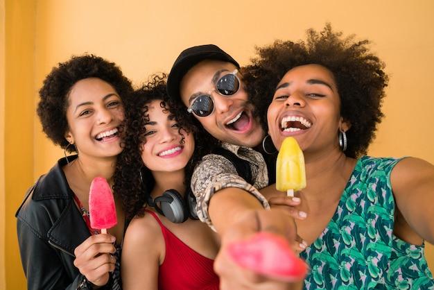 Gruppo multietnico di amici che godono l'estate mentre si mangia il gelato.