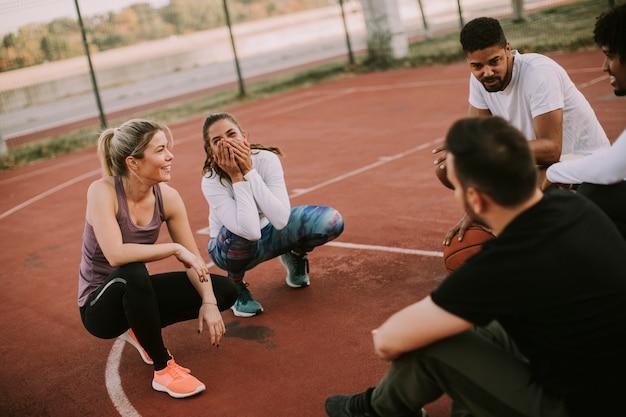 Gruppo multietnico di giocatori di pallacanestro che riposa sulla corte