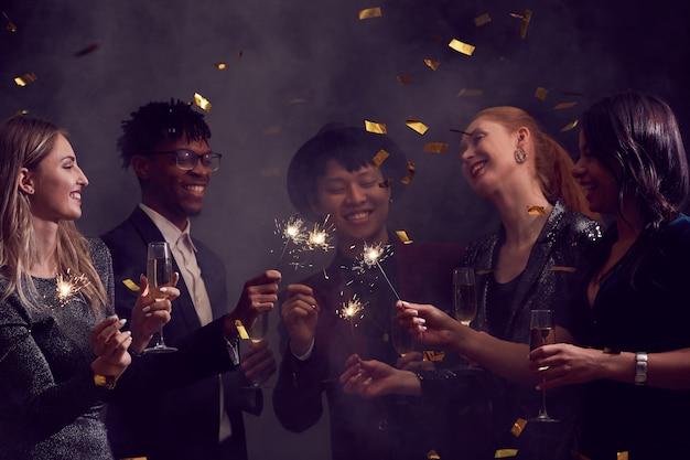 Gruppo multietnico di persone che celebrano in discoteca