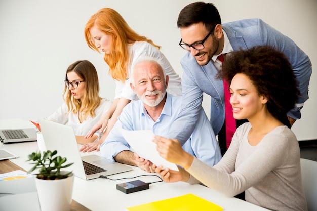 Gruppo multirazziale allegro di affari sul lavoro in ufficio moderno