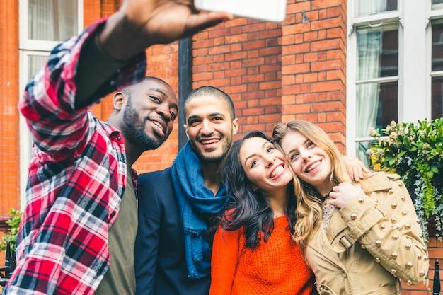 Gruppo multirazziale di amici che prendono insieme un selfie