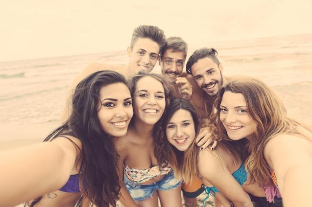 Gruppo multirazziale di amici che prendono selfie sulla spiaggia