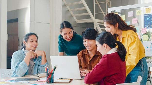 Gruppo multirazziale di giovani creativi in abbigliamento casual intelligente che discute di idee per riunioni di brainstorming di affari progetto di progettazione di software applicativo mobile in ufficio moderno. concetto di lavoro di squadra del collega.