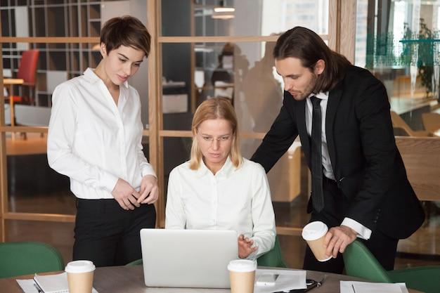 Gruppo serio concentrato di affari che discute insieme compito online nell'ufficio