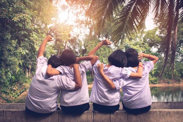 Gruppo teenager di studenti uniformi che si siedono e che abbracciano in un parco