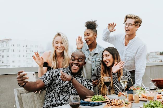 Gruppo vario di amici che prendono un selfie ad una festa sul tetto