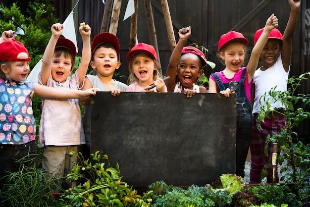 Gruppo vario di bambini allegri che tengono una lavagna