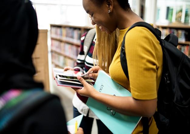 Gruppo vario di studenti delle scuole superiori in biblioteca