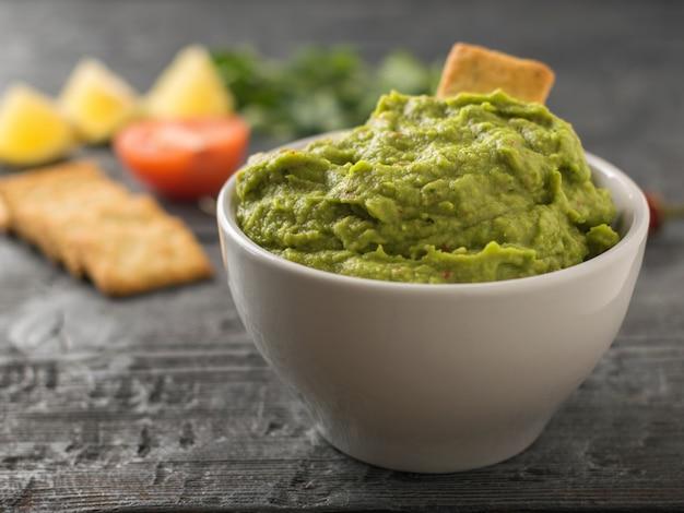 Guacamole appena fatto. mangiare avocado su un tavolo rustico. cucina vegetariana.