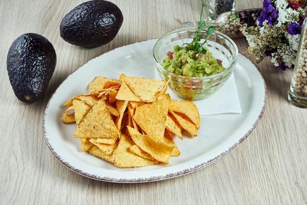 Guacamole di avocado con chip di nacho su un piatto leggero su un tavolo di legno. chiuda sulla vista sul popolare spuntino messicano