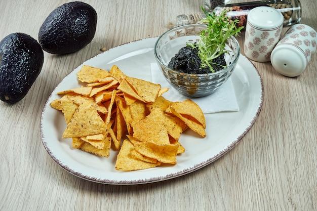 Guacamole di avocado nero con inchiostro di seppia e patatine di nacho su un piatto leggero su un tavolo di legno. chiuda sulla vista sul popolare spuntino messicano