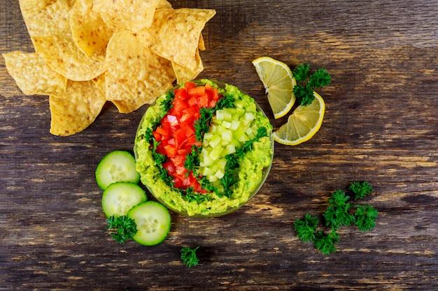 Guacamole fatto in casa con chips di mais e verdure vista dall'alto