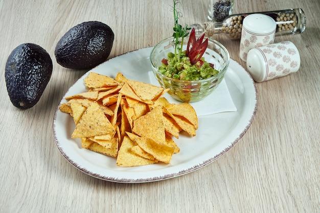 Guacamole piccante dell'avocado con i chip del nacho su un piatto leggero su una tavola di legno. chiuda sulla vista sul popolare spuntino messicano