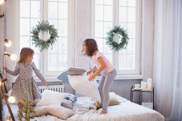 Guai ragazze, sorelle che combattono cuscini sul letto, la finestra decorata con una ghirlanda di natale, vita, infanzia