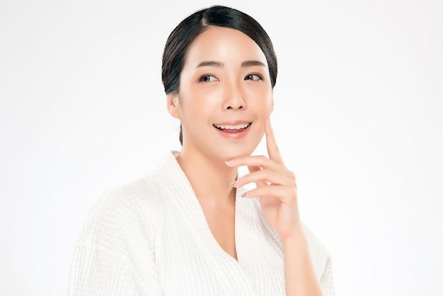 Guancia e tocco molli commoventi della bella giovane donna asiatica con pelle pulita e fresca. felicità e allegria con, isolato su bianco, bellezza e cosmesi,