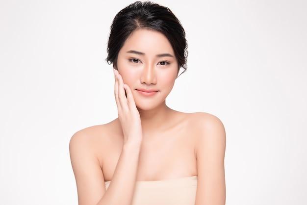 Guancia e tocco molli commoventi della bella giovane donna asiatica con pelle pulita e fresca
