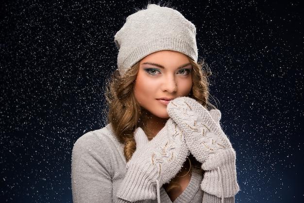 Guanti d'uso della ragazza riccia sveglia durante le precipitazioni nevose