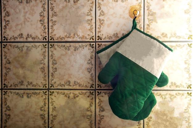 Guanti da forno verdi appesi al muro vecchio stile con motivi antichi di design pattern
